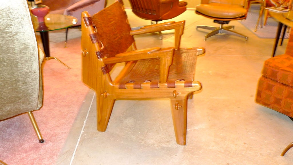 This chair came to exist out of a 1960's Peace Corps initiative to aid local crafts people in Ecuador, with the assistance of Scandinavian designers, to produce and export furniture using local woods and hand tooled leather.  The chair is held