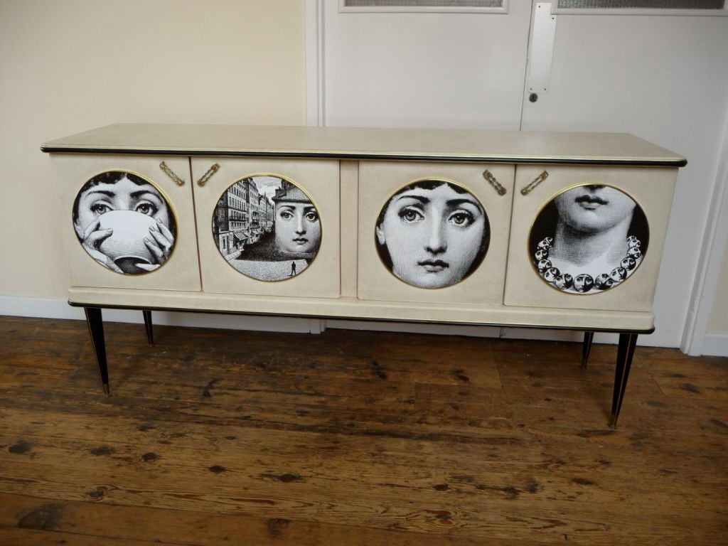 Six foot sideboard buffet designed by Umberto Mascagni of Bologna and retailed at Harrod's.  Case legs and doors covered in snow white skai.  Original glass top.  Laminated Fornasetti panels are a later embelishment.<br /> <br /> Legs remove for