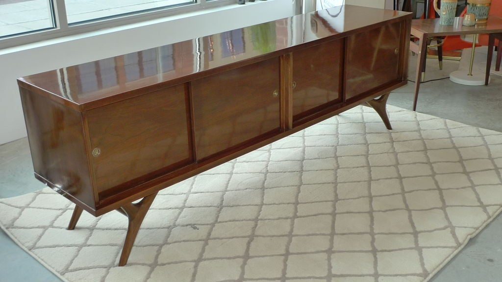 Long low case credenza with four sliding doors which open to two compartments, one with an adjustable shelf.
