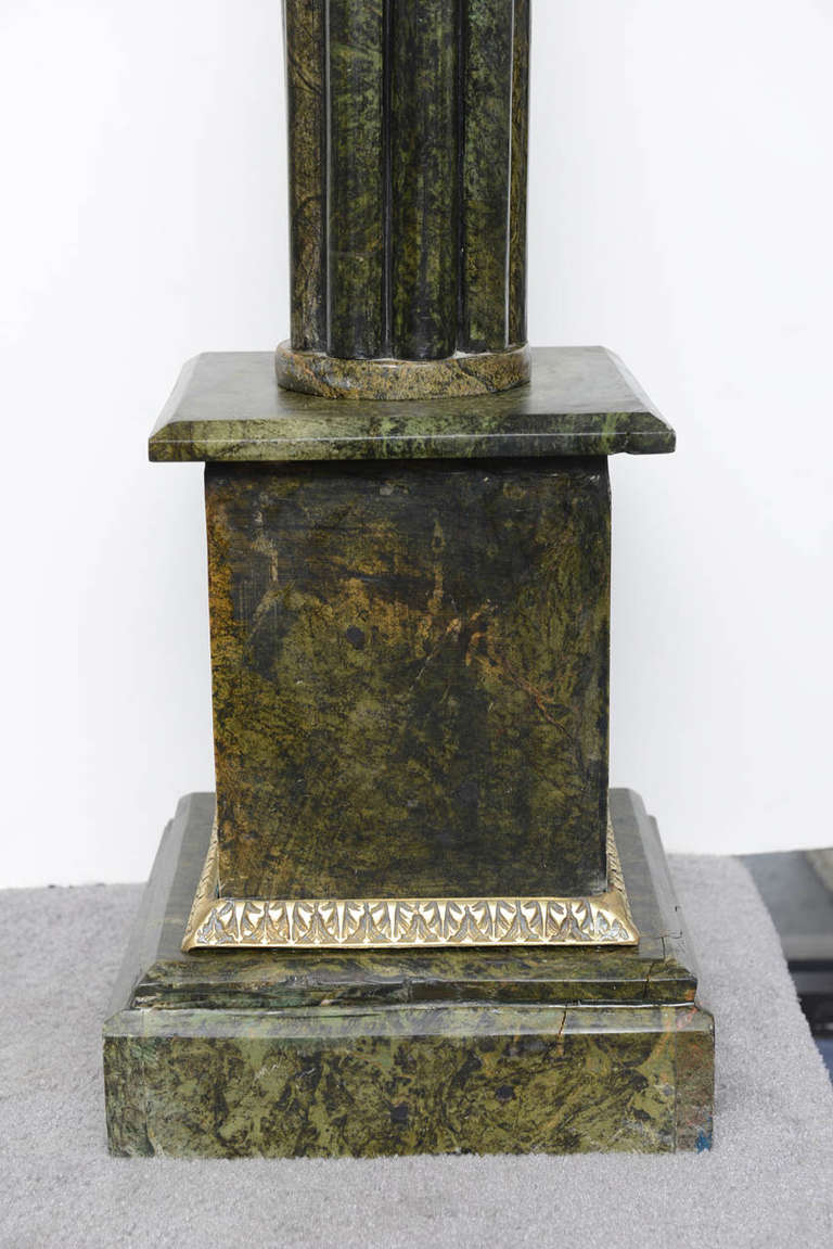 Neoclassical style  marble pedestal, built on a square marble base. The base is surrounded by a strip of bronze ornaments. Nine thin marble columns form all together the main column which support a square marble top.  Small restoration on the base.