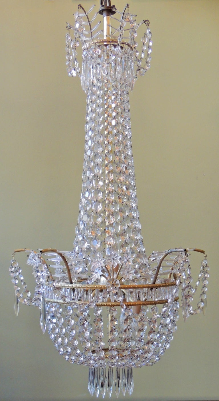 A 1920's French chandelier, featuring bronze structure with a patterned bronze ring, beautiful star, feather crystal beads, and graduated prisms throughout. This piece has been recently refurbished and rewired.