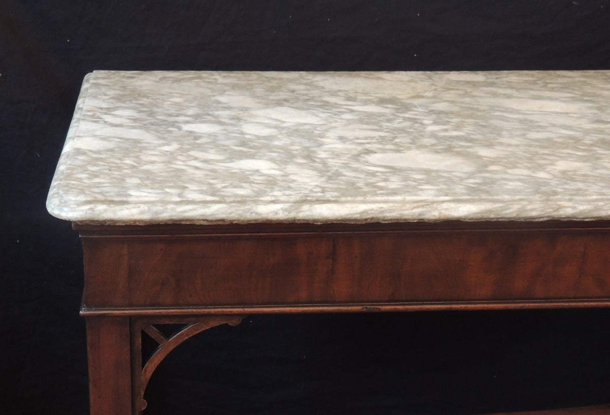 This English Chippendale style table was made in the mid-18th century, circa 1760 It has a mahogany body with Marlborough legs and simple open fretwork brackets. The tabletop is a massive piece of beautiful hand-chiseled, gray-veined marble, and is