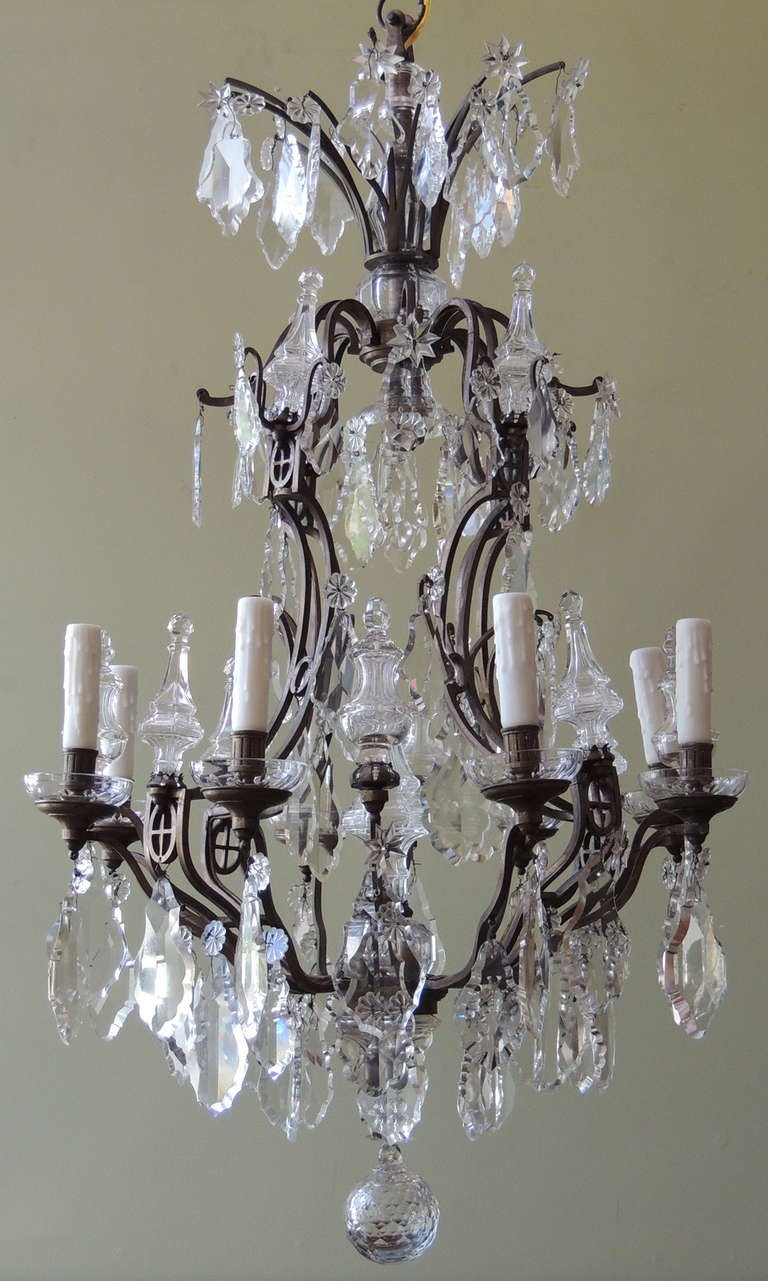 A large iron and crystal French early-20th century chandelier. This piece features eight arms, Baccarat-quality crystal prisms and a birdcage style frame. Recently cleaned, rewired and ready for installation.