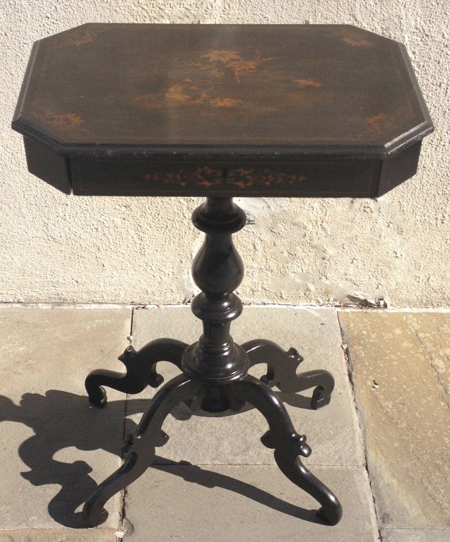 A beautiful English Regency ladies work table. This piece features scrolled feet, turned center post, and a hand painted table top in a beautiful chinoiserie style. This piece also features a drawer with multiple compartments.