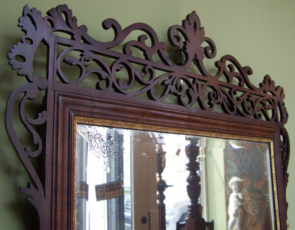 A Dutch Queen Anne mirror from the mid 18th century, circa 1750, with finely carved mahogany filigree, giltwood accents and original mirror.