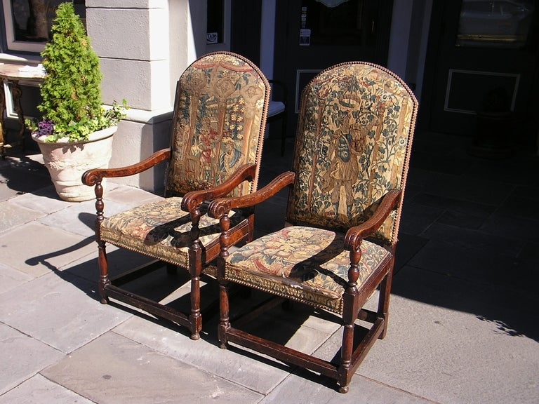 Pair of Italian walnut armchairs with arched top, floral carved scrolled arms,  original needlepoint, and terminating on bulbous turned legs with stretchers. 18th Century