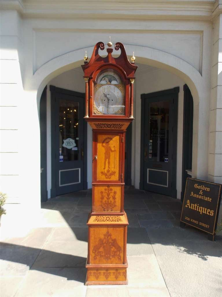 English mahogany tall case clock with scrolled pediment, brass finials, Corinthian columns, and intricate inlaid motif. Mid 19th Century