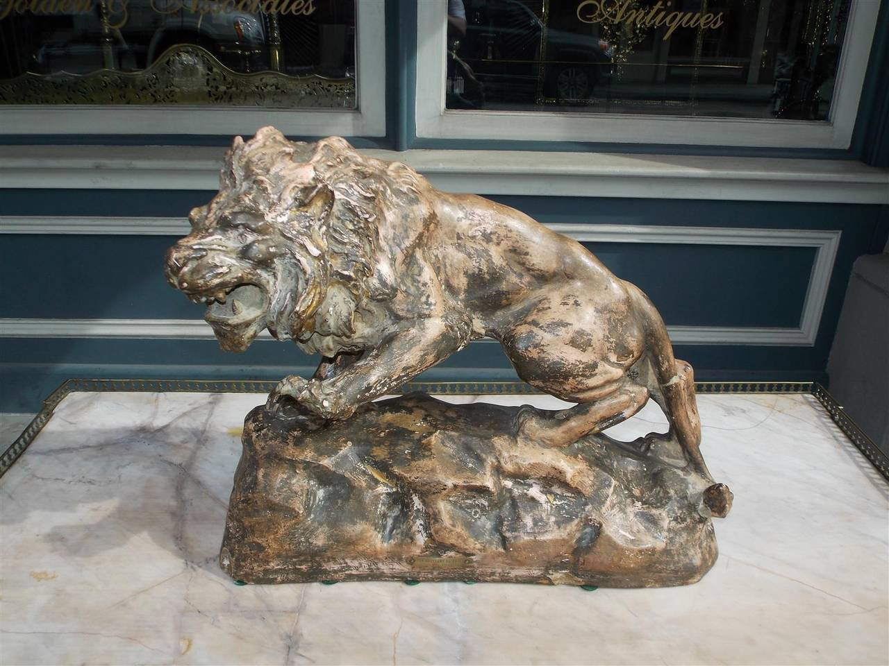 French Terracotta roaring lion mounted on rocky rectangular plinth.  Plaque reads Lion Guettant Sa Proie, Par Foucher.  Late 19th Century