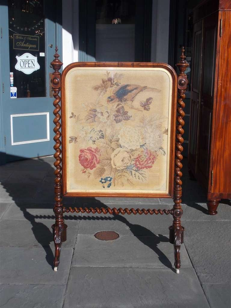 English Kings Wood fire screen with urn finials, barley twist supports, original needlepoint with bird and floral motif, terminating on scrolled acanthus legs with original porcelain casters.  Mid 19th Century