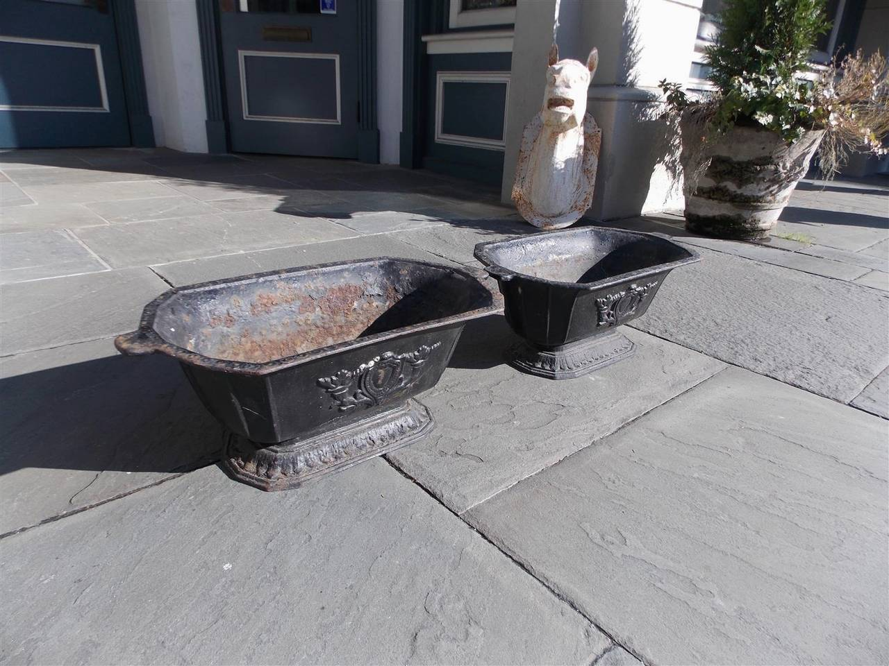 Pair of American cast iron rectangular floral crest planters with lambs tongue motif, Late 19th century.