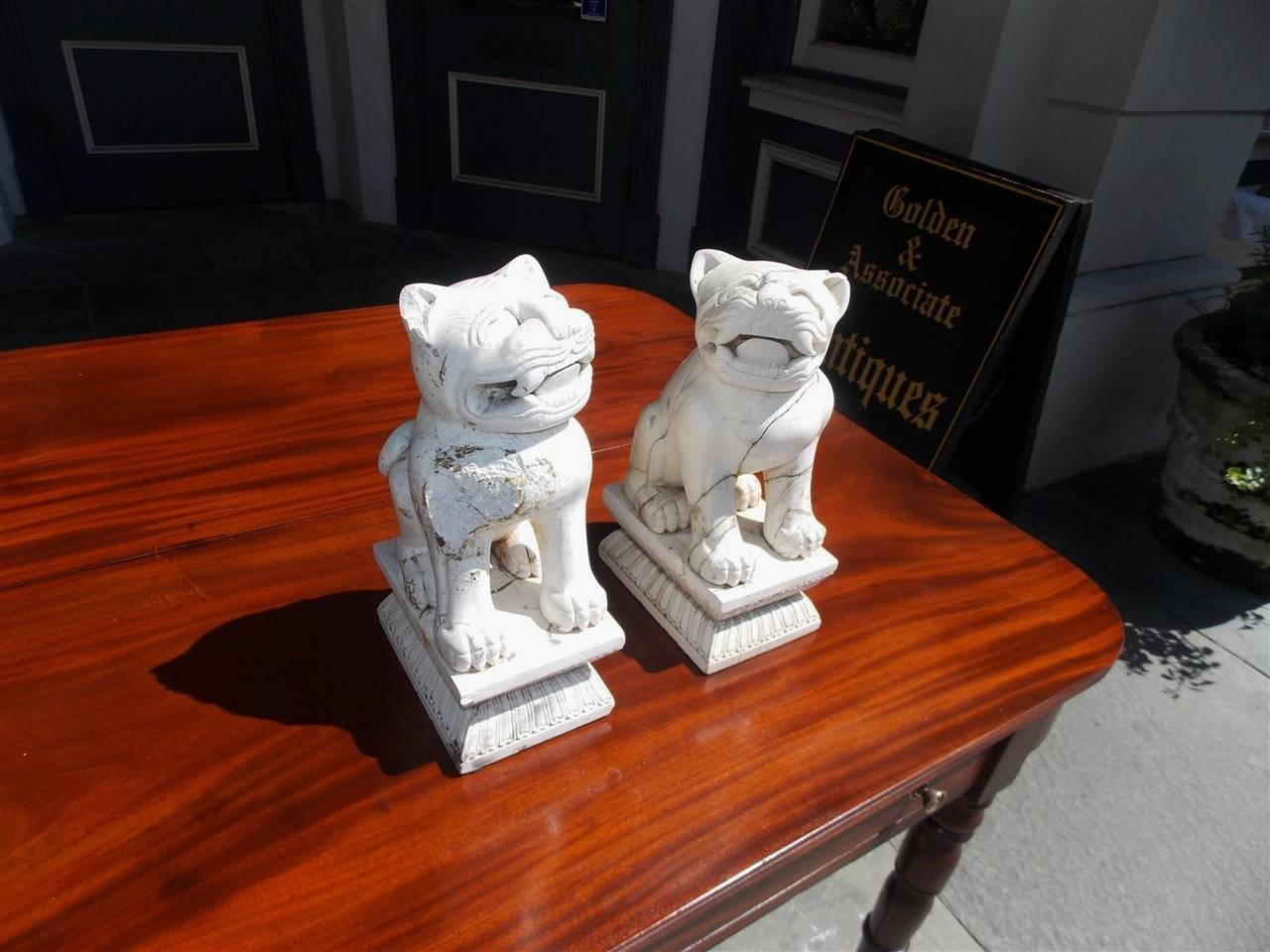 Pair of hand carved Chinese stone sitting Foo dogs resting on rectangular decorative carved plinths. Mid-19th Century.