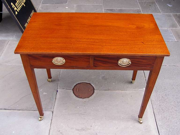 English mahogany two drawer writing table with one board top, lions head pull brasses, and terminating on tapered legs with original brass casters. Late 18th Century.