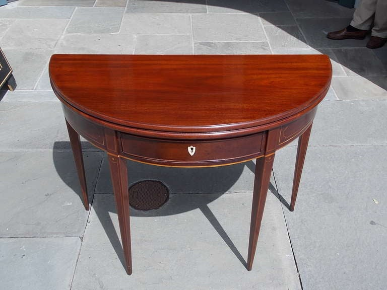 English mahogany one drawer flip top demi-lune game table with one board top, Satinwood string inlay, original key escutcheon, and terminating on double gate tapered squared legs.  Late 18th Century