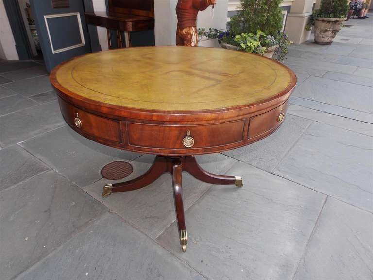 English Regency mahogany four drawer rent table with leather top, original pulls, bulbous pedestal, and terminating on saber legs with original brass casters. Late 18th Century