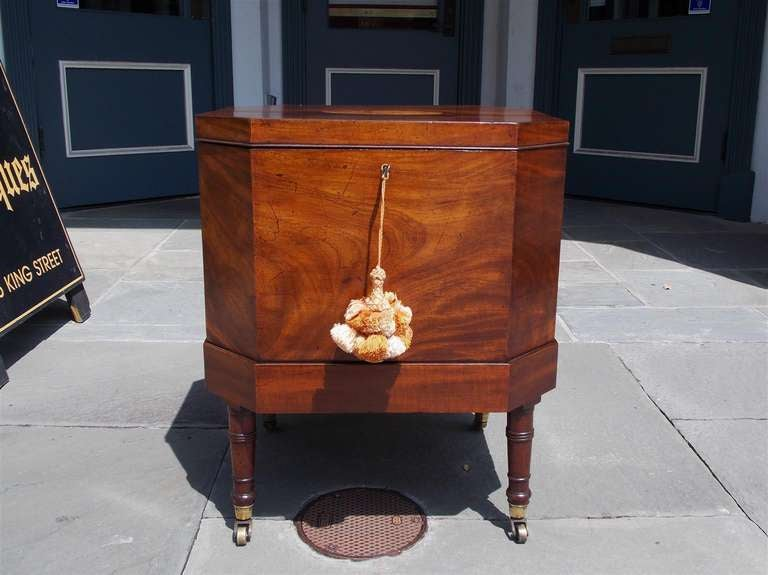 English mahogany wine cellarette with inlaid Satinwood conch shell, hinged top revealing a compartmentalized fitted interior, and terminating on the original turned legs with brass casters. Late 18th Century