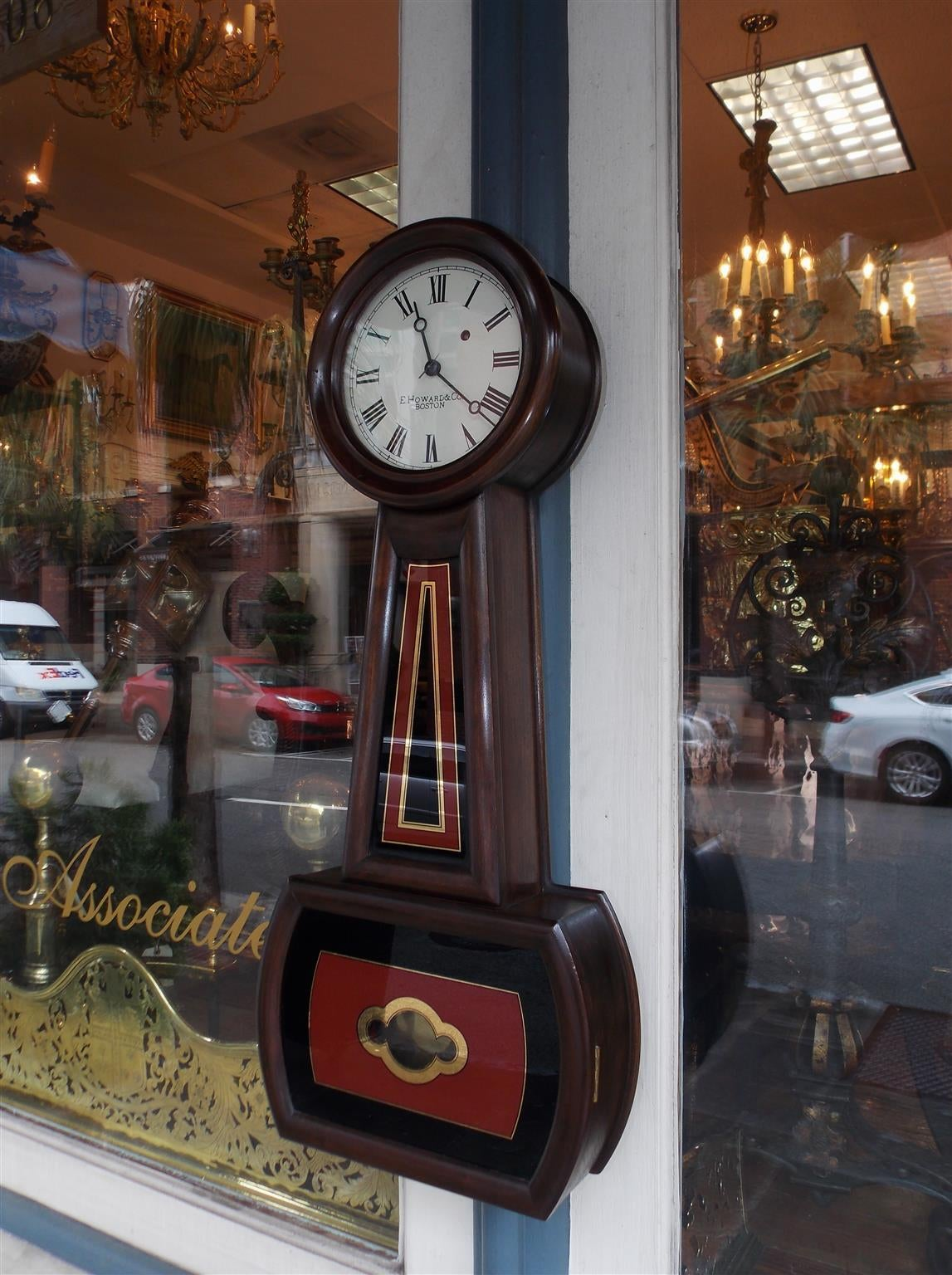 American mahogany and églomisé banjo clock with original signed and numeral paper dial under glass, decorative painted and gilt throat panel, with a hinged painted and gilt door concealing the brass pendulum. Clock is in working condition. Signed