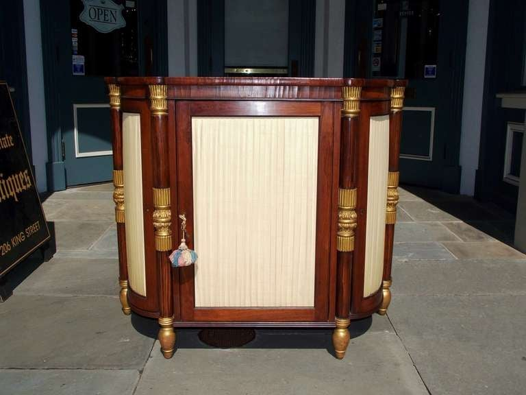 Italian rosewood and gilt three door console with gilt carved floral mounts, pleated upholstered wooden doors, and terminating on gilt bulbous feet.  Dealers please call for trade price.