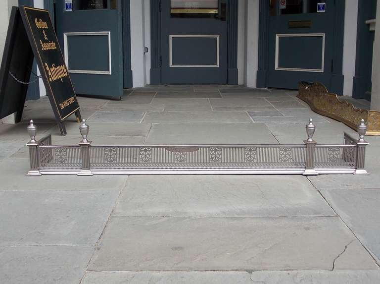 English Polished Steel and Nickel Silver Fire Fender adorned with with hand chased urn finials, chased pierced floral gallery with single row of beading, ending on squared plinths. Dealers please call for trade price.