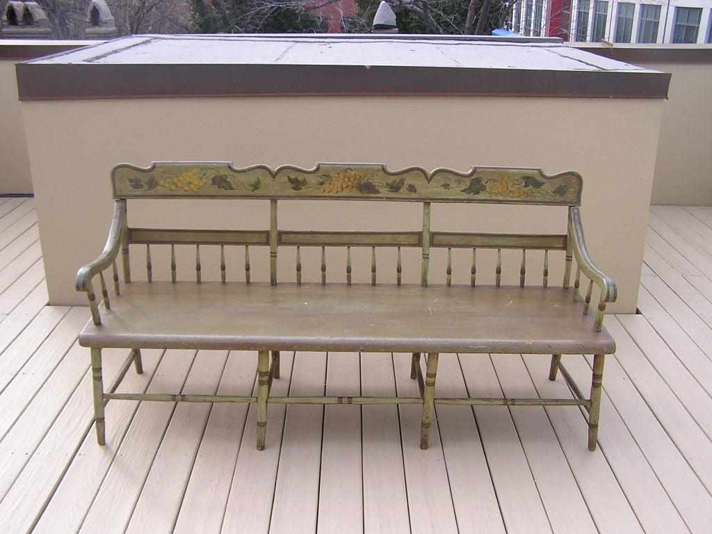 American carved wood and painted bench with grape vine motif, one board seat, scrolled arms, spindle carvings, and ending on turned painted legs. Fancy Furniture, Baltimore.  Early 19th Century.