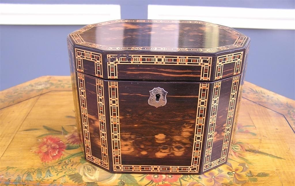 English Coromandel flip top tea caddy with boxing satinwood inlay, original nickel silver escutcheon,  and the original tin liner with lid. Original paper label affixed to bottom. Maker,  Edmund Nye Tun bridge Wells. Early 19th Century