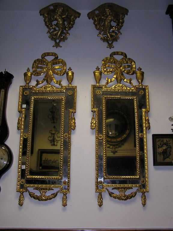 Pair of Italian gilt carved wood wall mirrors with ribbons , flanking urns , medallions , & floral swags . Late 18th Century.  Mirrors retain the original glass & wood back .