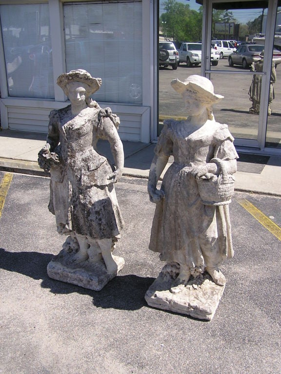 Pair of English hand carved sandstone figural garden statues of ladies holding a fruit basket and floral bouquet. Late 18th Century