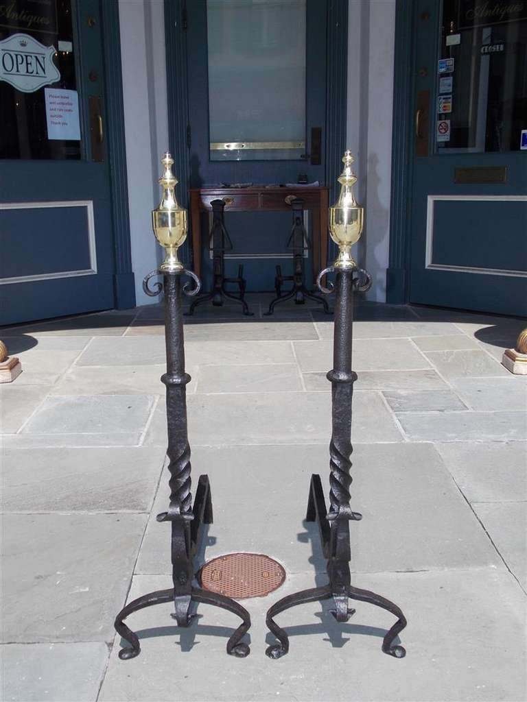 Pair of American wrought iron and brass urn finial andirons with scrolled twisted center column, terminating on scrolled legs with penny feet. Center column was derived from axles of a horse drawn carriage.  Late 18th Century