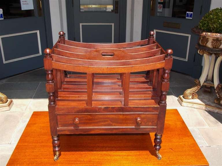 English mahogany one drawer canterbury having bowed framed mahogany divisions, carved corner roundels, and raised on turned bulbous legs with original brass casters.  Dealers please call for trade price.