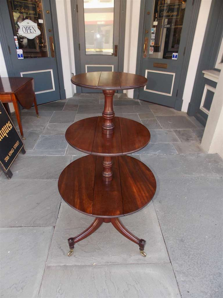 English mahogany three tier dumb waiter with hinged tops, bulbous turned center column, and terminating on reeded splayed legs with original brass casters. Late 18th Century