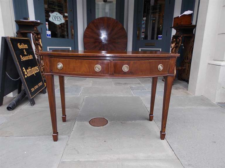 English Hepplewhite mahogany two drawer bow front server with Satinwood and ebony string inlay terminating on tapered spade legs. Late 18th century.