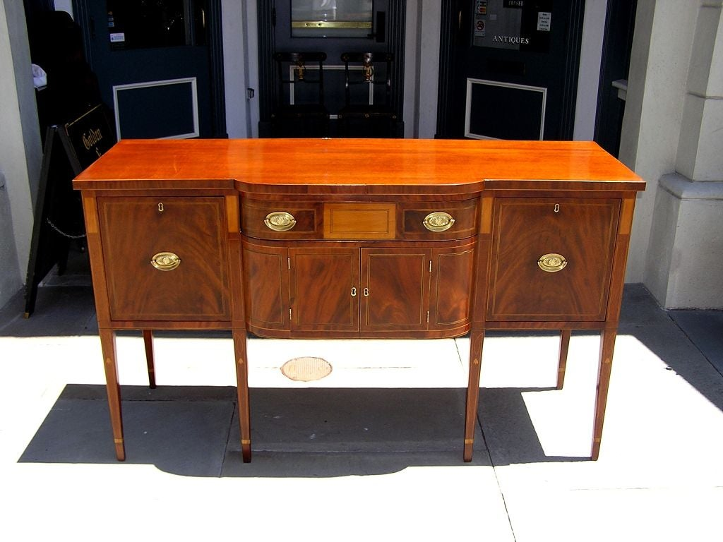 Charleston Classical Hepplewhite mahogany sideboard with figured crotch mahogany drawer fronts, satinwood string inlaid bell flowers with dots, and terminating on tapered legs with cuffed feet. Keys in drawer and secondary wood consist of White