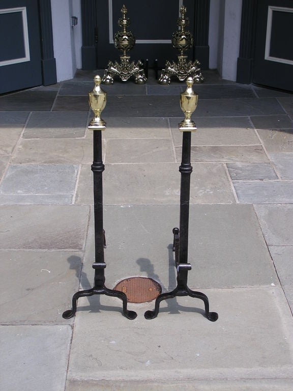 Pair of American wrought iron andirons with brass urn finial tops, scrolled decorative spit hook , and terminating on penny feet. Columns of andirons were originally used for axle's on a horse drawn carriage. Late 18th Century