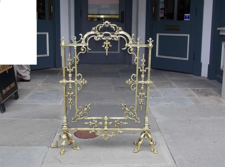 French brass free standing firescreen with flur-de-le finials, scrolled decorative floral and rope motif, and terminating on  fluted scrolled quad legs.  Dealers please call for trade price.