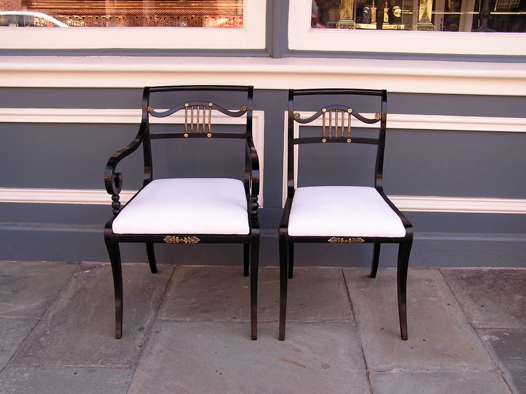 Set of eight English Regency painted and gilt dining room chairs with original center mounted ormolu terminating on saber legs. Chairs have original seat frames. Two arms & six sides.