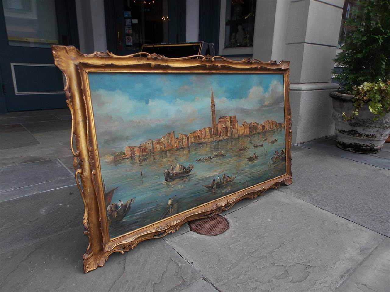 Venetian oil on board painting of the Island of Burano off the coast of Venice in original gilt floral carved wood frame.  Signed Prof. Mario Cora in lower right corner.  Paper label with signature on back as well.  18th Century