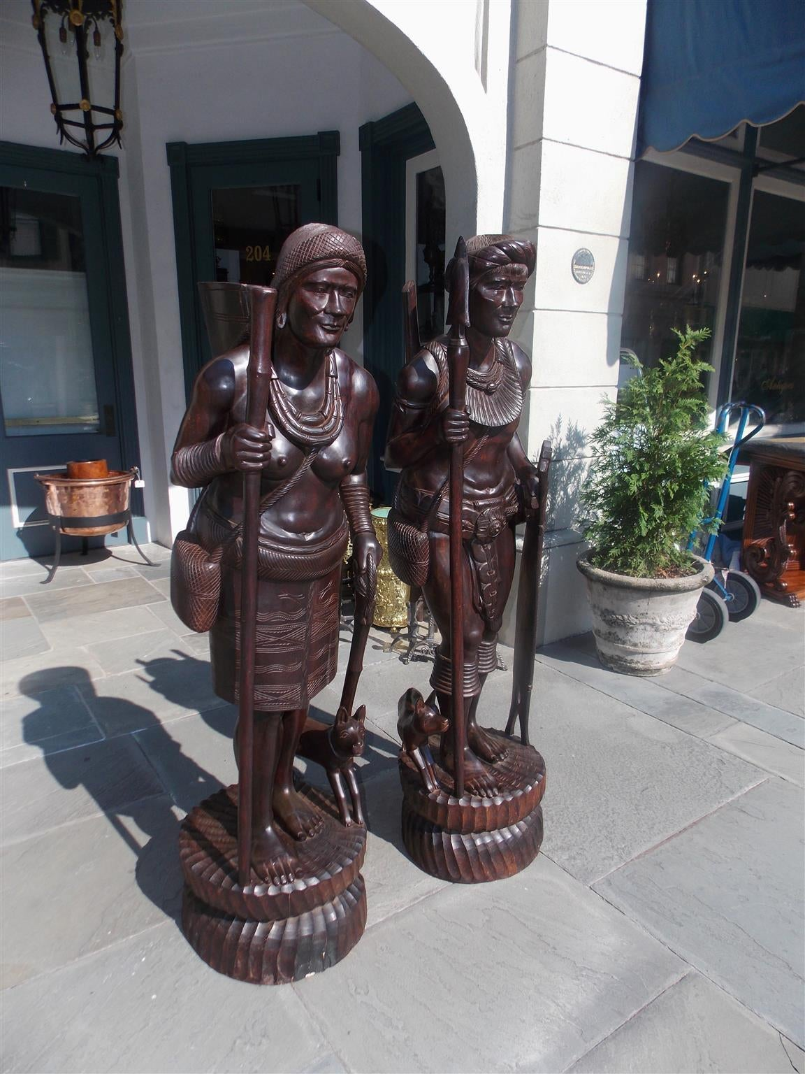 Pair of Igorot tribesmen figural wood carvings depicting hunter and huntress with companion canines, weaponry, and displayed on circular fluted plinths. Northern Luzon , Philippine Islands . Were feared & known as deadly head hunters. Early 20th