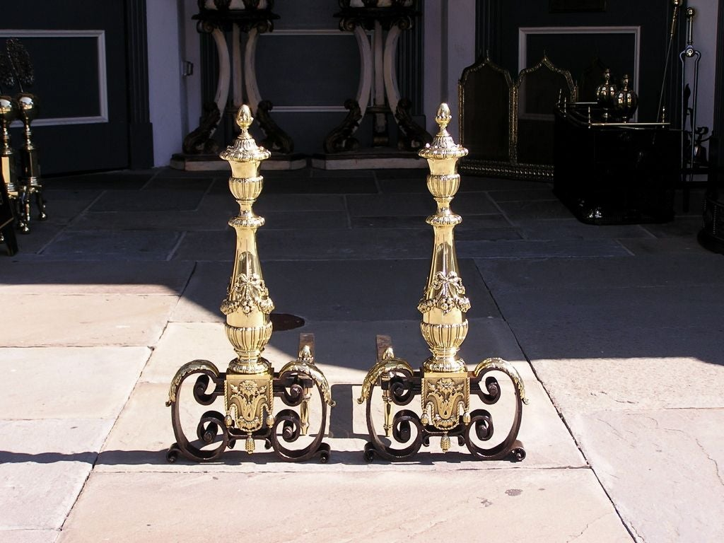 Pair of Italian brass and wrought iron andirons with decorative flanking urn acorn finials, bulbous gadrooned floral ribbon columns, matching finial log stops, and terminating on scrolled acanthus legs with tassel and foliage motif.  Early 19th