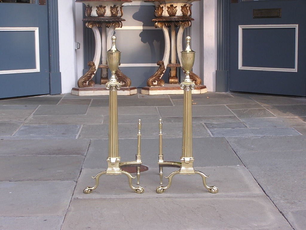 Pair of American brass urn top andirons with fluted Roman Ionic Square Capitals, spit hook, spur leg with claw & ball feet, and matching urn finial log stops.