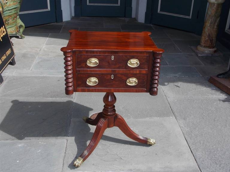 American mahogany two-drawer work table with fitted interior, out set corners supported by turned ringed columns, terminating on a bulbous turned pedestal with reeded splayed legs and original brass paw casters. Boston, Early 19th Century.