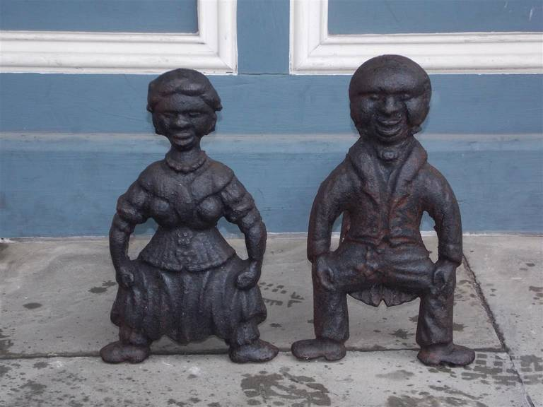 Pair of American cast iron squatting figural andirons of man and woman with original dog legs. Mid 19th Century