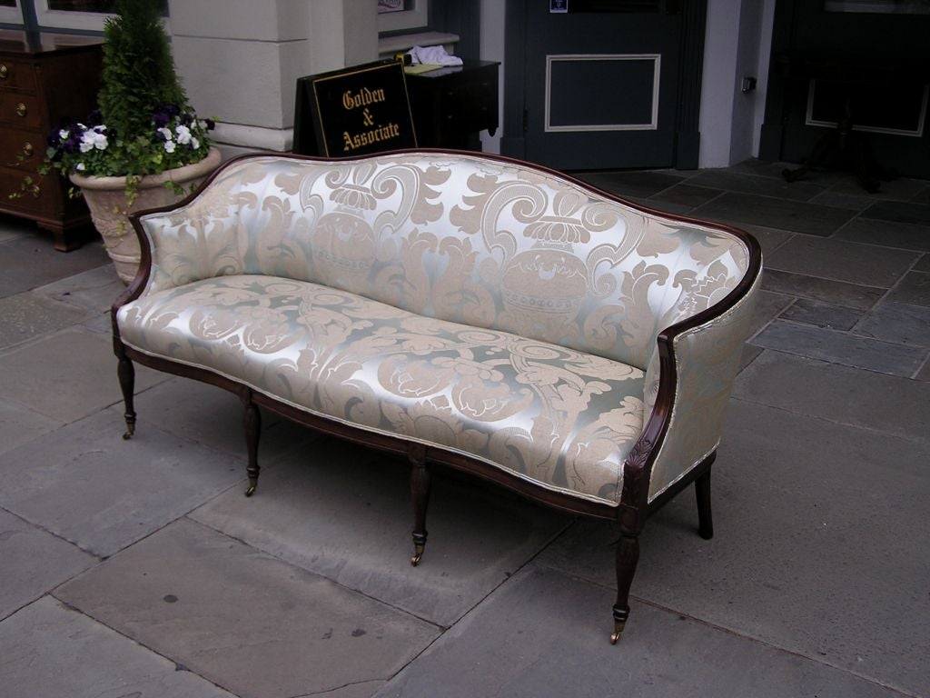 American mahogany sofa with serpentine shaped arms, frontal skirt & back, carved acanthus leaf knees, and terminating on carved floral bulbous legs with original brass casters. Massachusetts