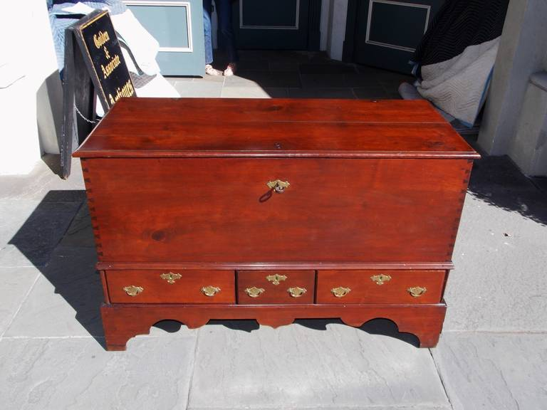 American Queen Anne Walnut lower case three drawer blanket chest with original wrought iron hinges, exposed exterior dovetails, original engraved brasses, fitted interior till, and terminating on carved skirt with original bracket feet.