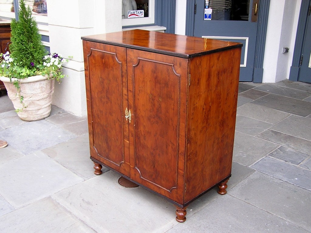 English Yew Wood two door chest of drawers with ebonized reeded molded edges, original fitted interior drawers,original brass hardware, and terminating on original turned bulbous feet.