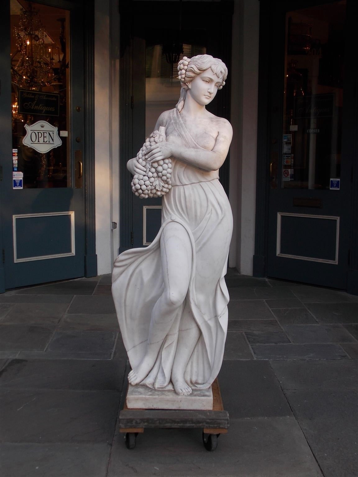 Italian marble figure statue of standing woman grasping cluster of grapes resting on squared plinth. Mid 19th Century