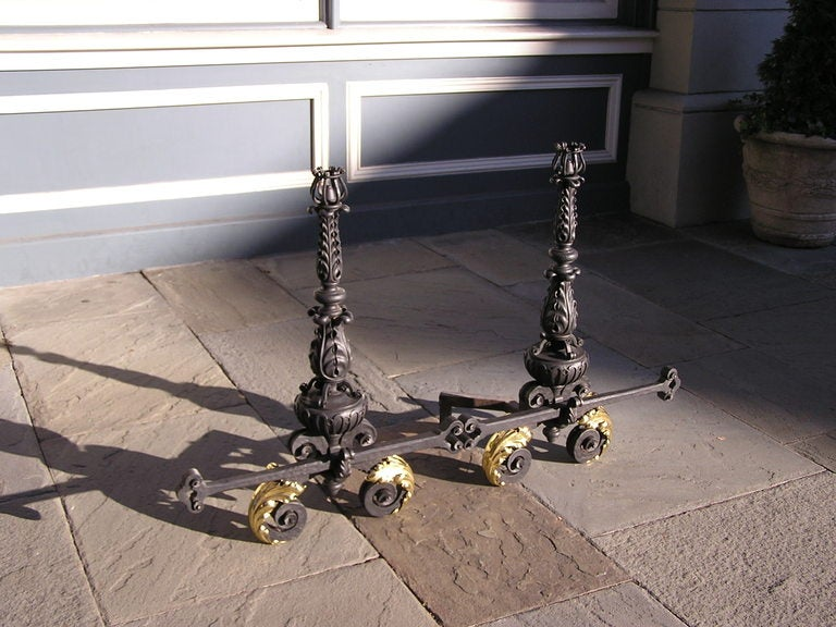Pair of Italian wrought iron and brass andirons with decorative floral motif, decorative centered cross bar, and terminating on scrolled legs. Dealers please call for trade price.