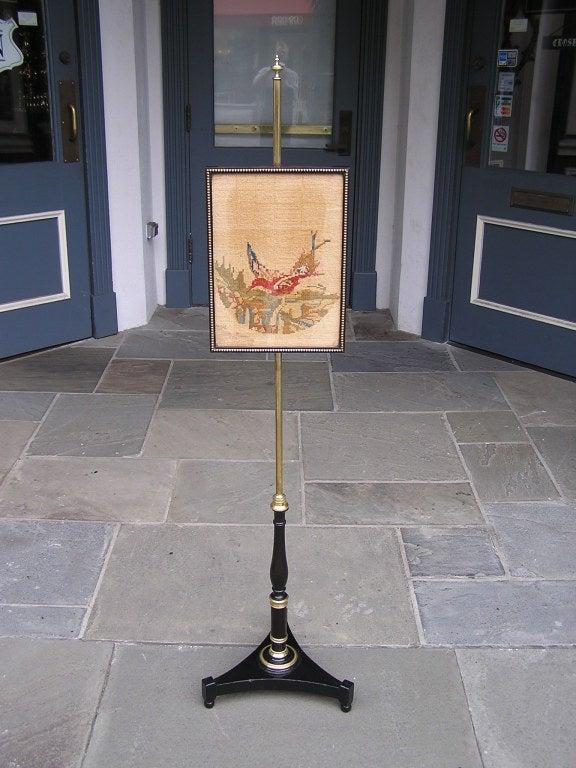 English Regency brass pole screen with adjustable framed needlepoint of bird resting on nest terminting on tripod ebonized base.