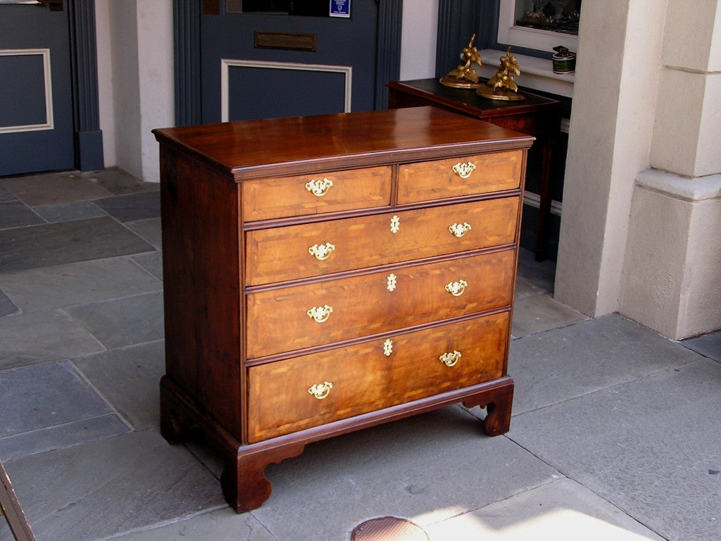English walnut graduated five drawer chest with inlaid walnut and rosewood drawer fronts terminating on bracket feet.