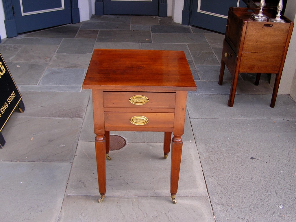 American Cherry two drawer stand with one board top, turned squared tapered legs, and terminating on original brass casters. New York