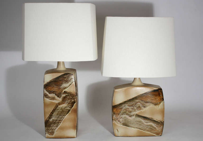 Pair of ceramic table lamps with a bold and striking glaze decoration. Each lamp has a custom made shade that mirrors the shape of each lamp base. Both lamp bases and shades are in excellent condition. Circa 1970s.  Smaller lamp dimensions: 30