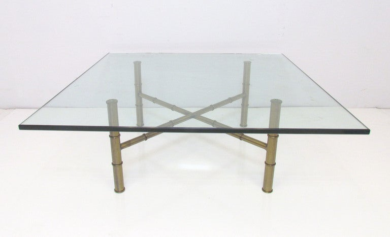 "Minimalist in the manner of a Barcelona table, but with an elegant regency flair --an X-form coffee table in bronzed metal with faux bamboo legs and stretchers supporting a ¾"" thick plate glass top."